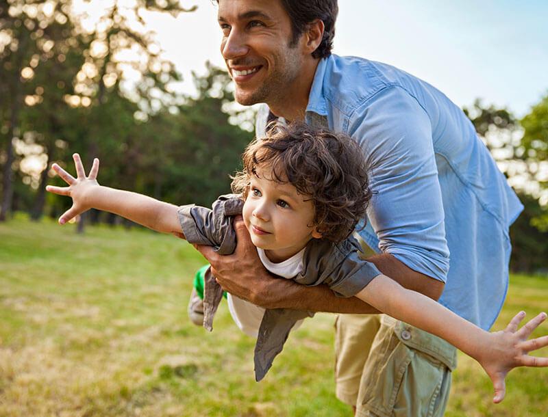 Mann spielt mit Kind auf Wiese