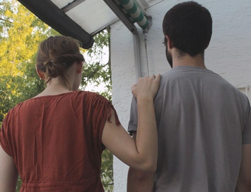 Frau hat ihre Hand auf der Schulter eines Mannes