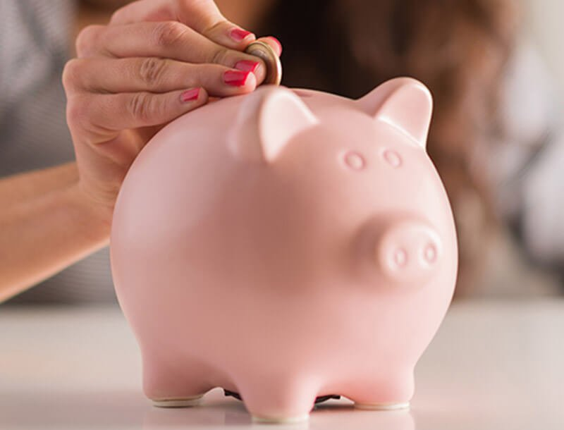 Frau  steckt Geldstück in Sparschwein